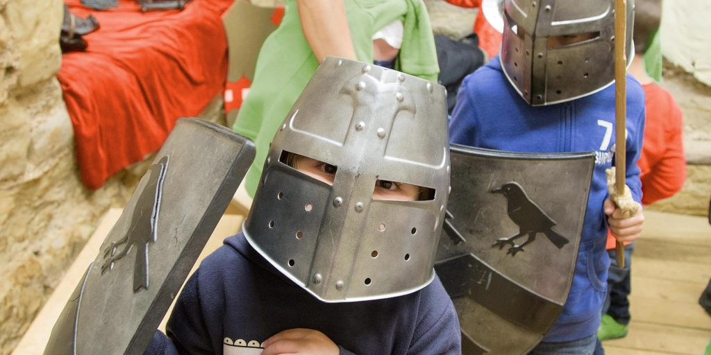 Kids in knights outfits at a castle