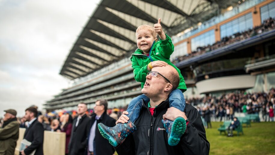 Toddler on father's shoulders at Ascot