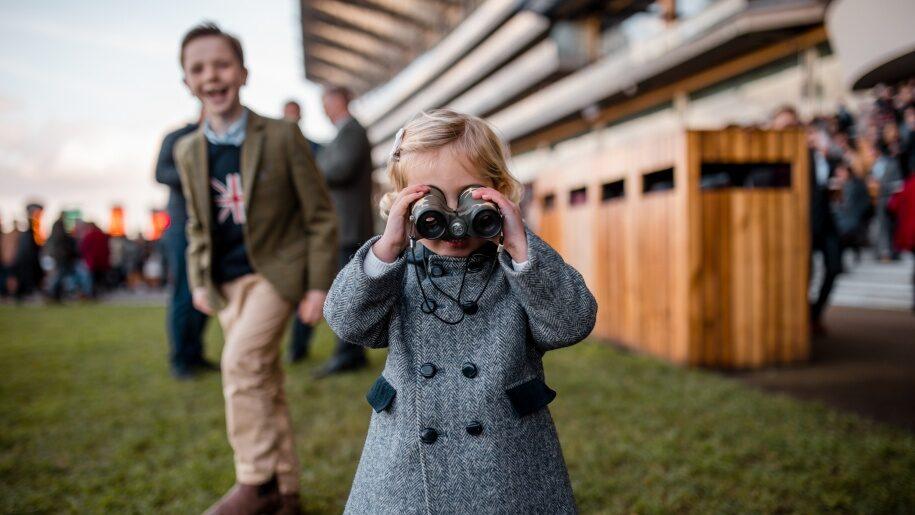 Young girl looking through binoculars at Ascot