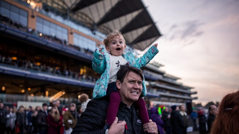 Toddler on father's shoulders watching racing at Ascot