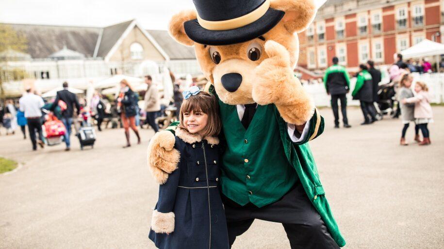 Girl with life-size Greencoat Bear mascot at Ascot