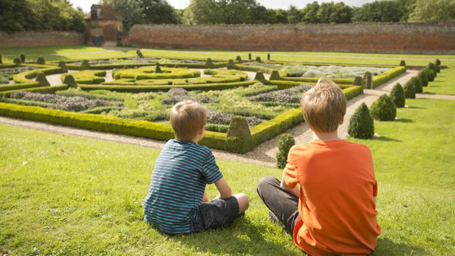 children sitting in formal gardens