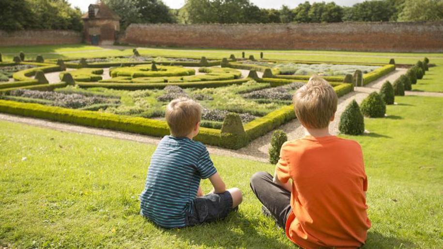 children sitting in formal gardens