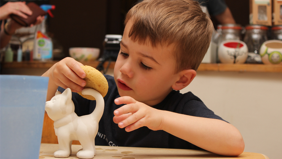 boy with biscuit and figurine of cat