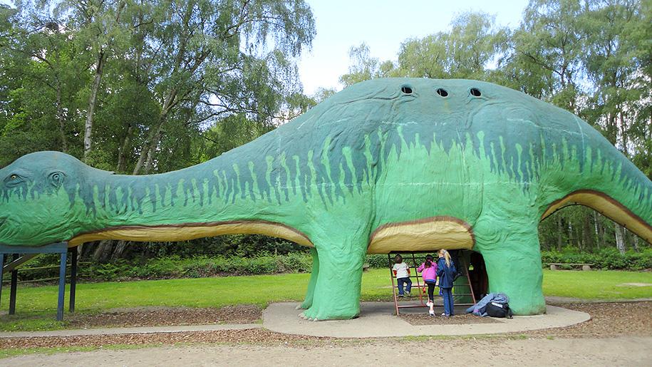 children climbing into a dinosaur