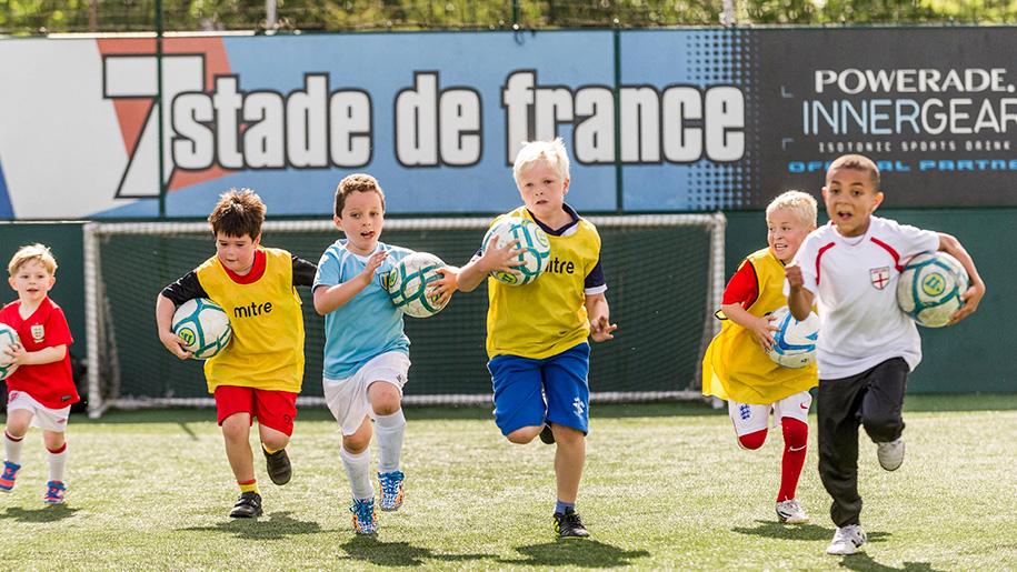 children running on football pitch