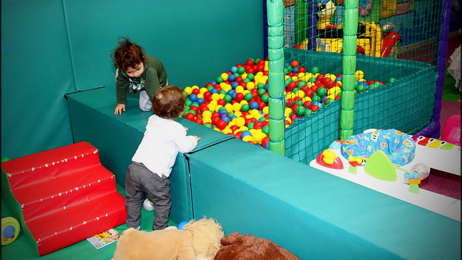 children climbing into ball pool