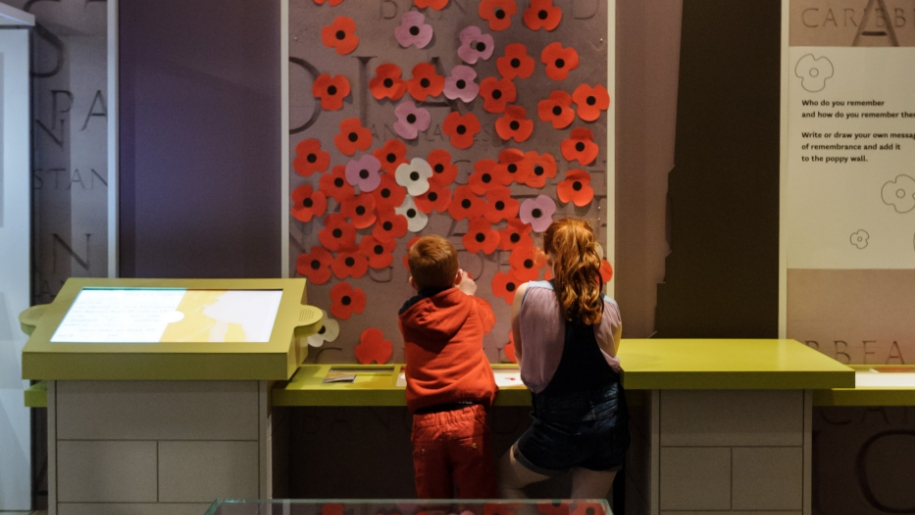 children at remembrance wall with poppies