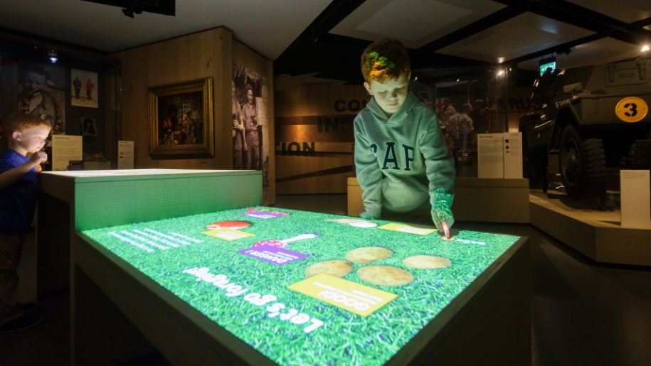 young boy playing on interactive table
