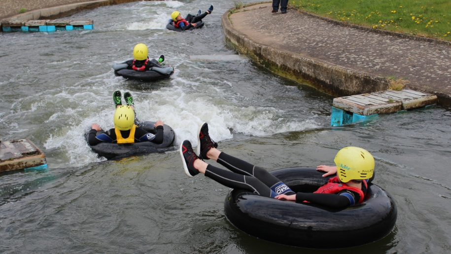children on rubber rings in water