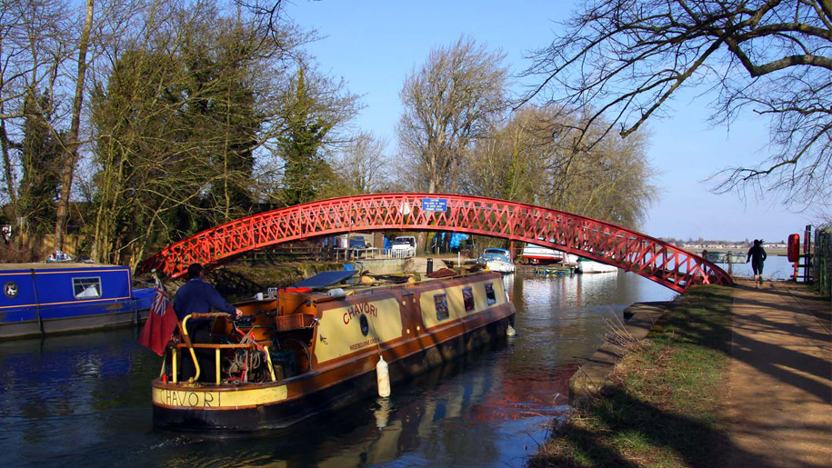 narrow boats on river under red bridge
