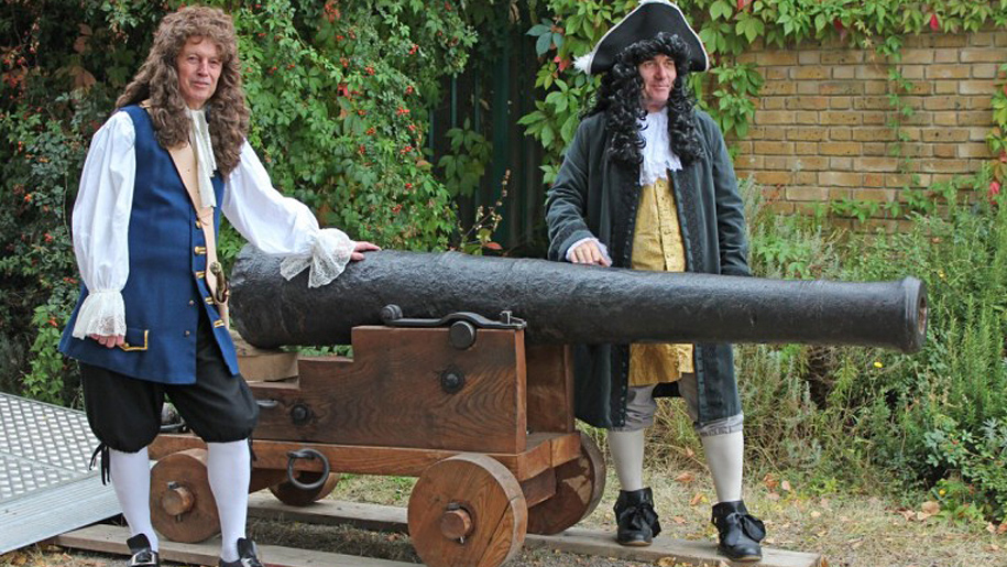 men in period dress standing by a cannon