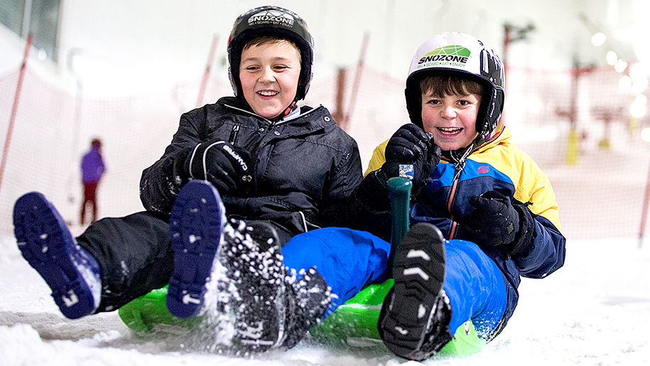 boys sliding down ski slope