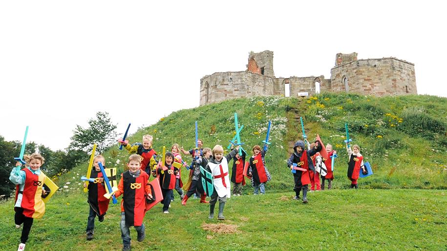 children dressing up outside castle