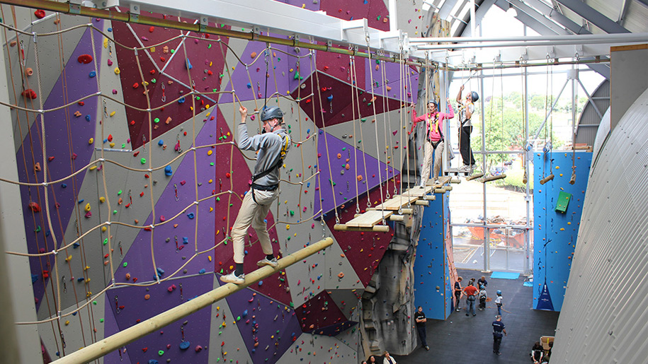 people on high ropes by rock climbing wall
