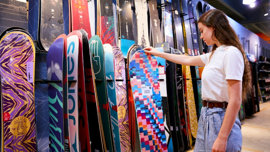 girl looking at snowboards