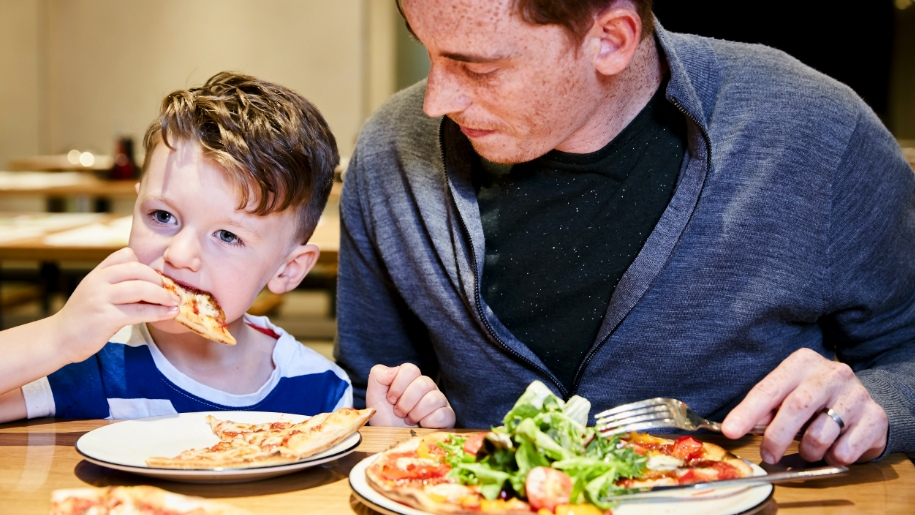 child and parent eating pizza