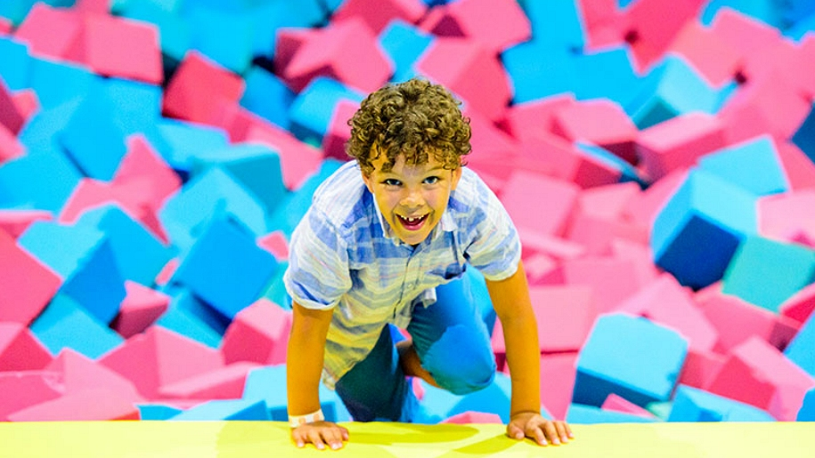 boy climbing out of foam pit
