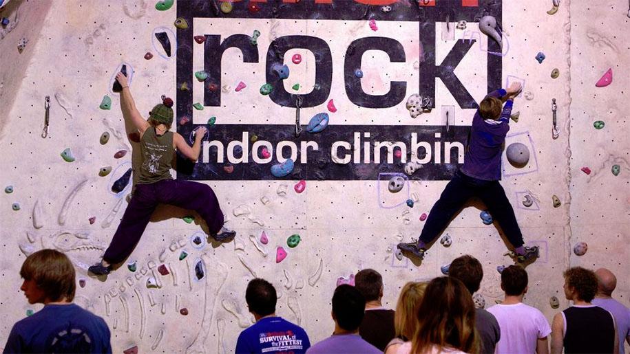 people climbing rock wall