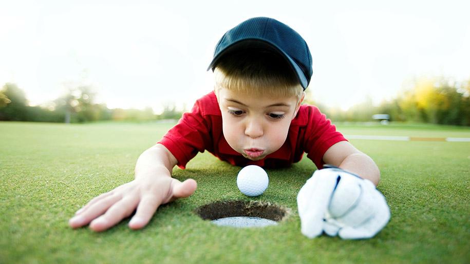 boy blowing golf ball into golf hole