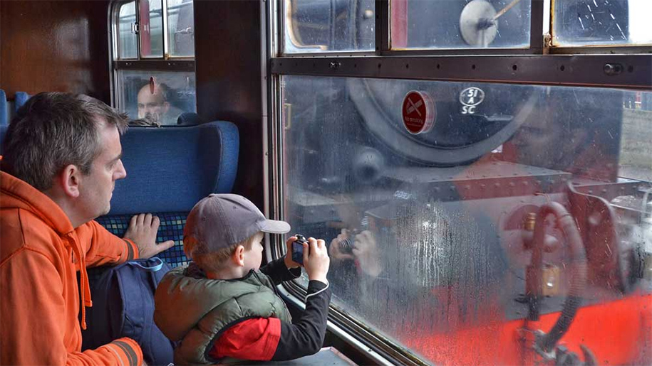 child taking photo of trains