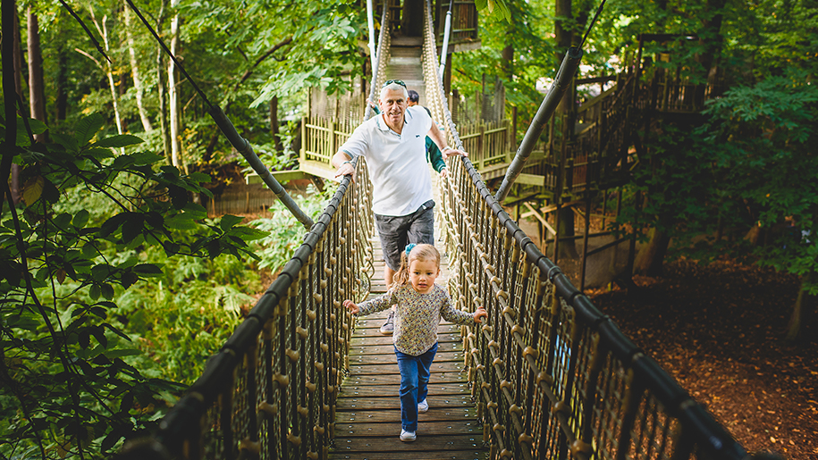 child and adult running across bridge