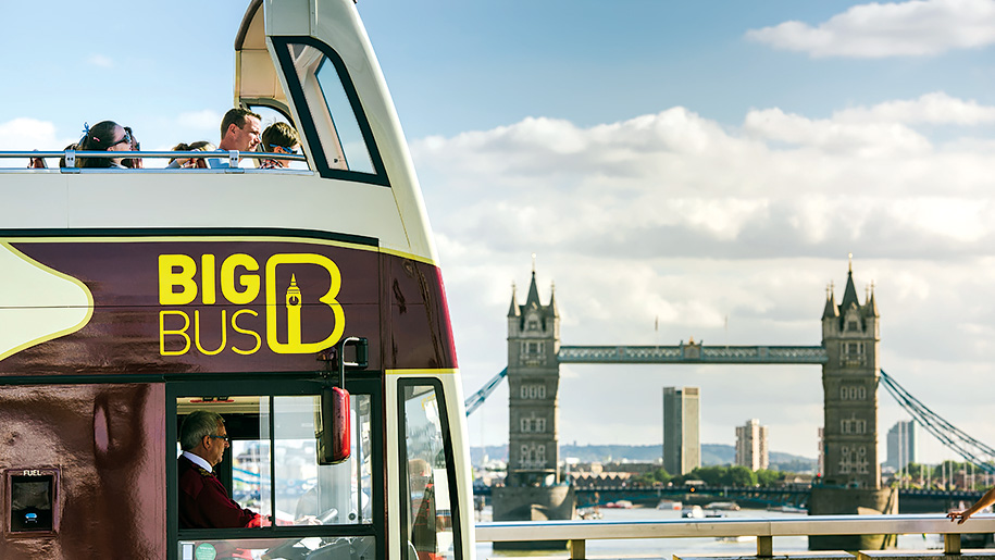 open top bus driving past Tower bridge
