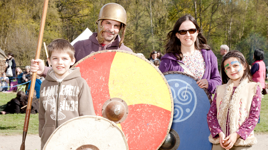man with round shield with boy and mother