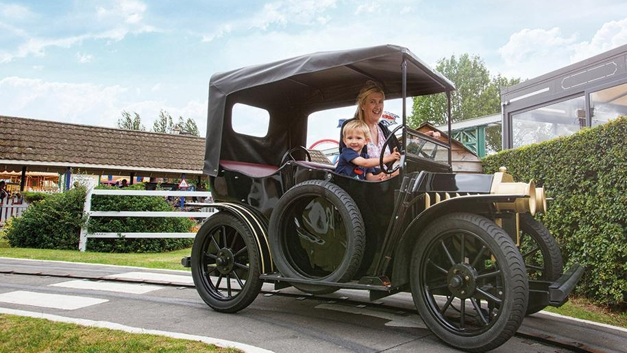child and adult in classic car