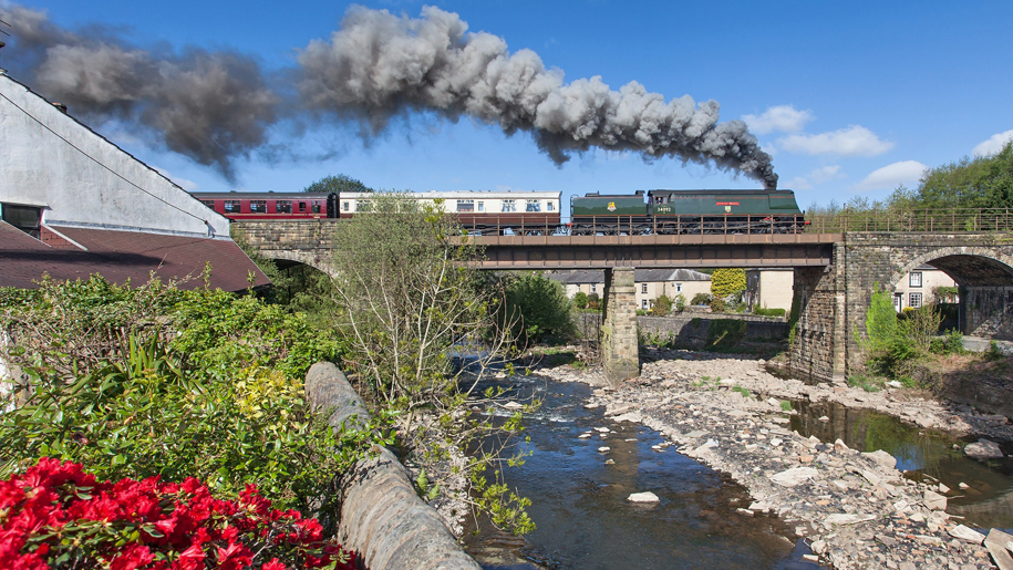 steam train going over bridge in sunshine