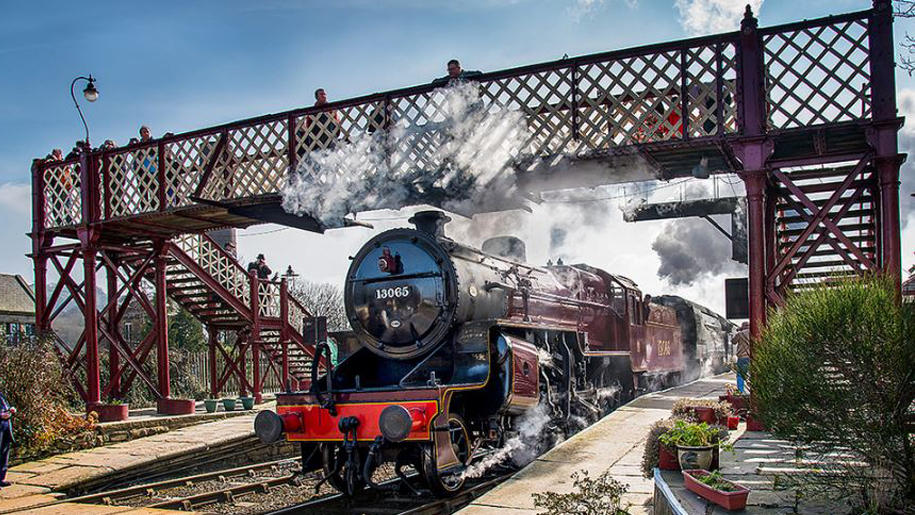 steam train going under bridge