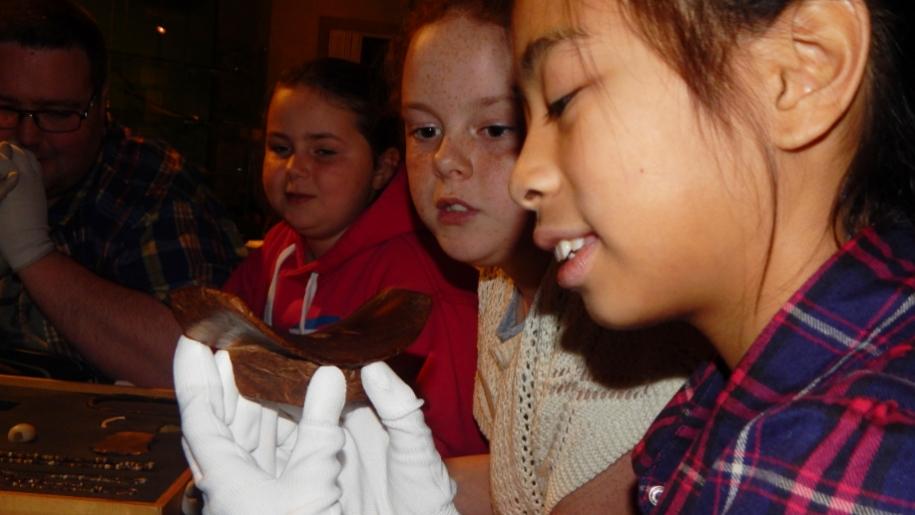 girls looking at artefact
