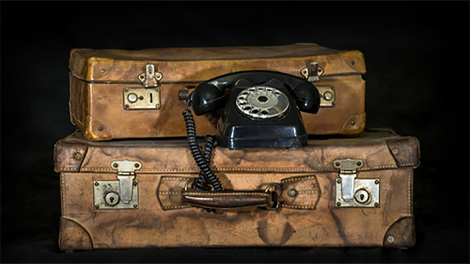 phone on two old revelation suitcases