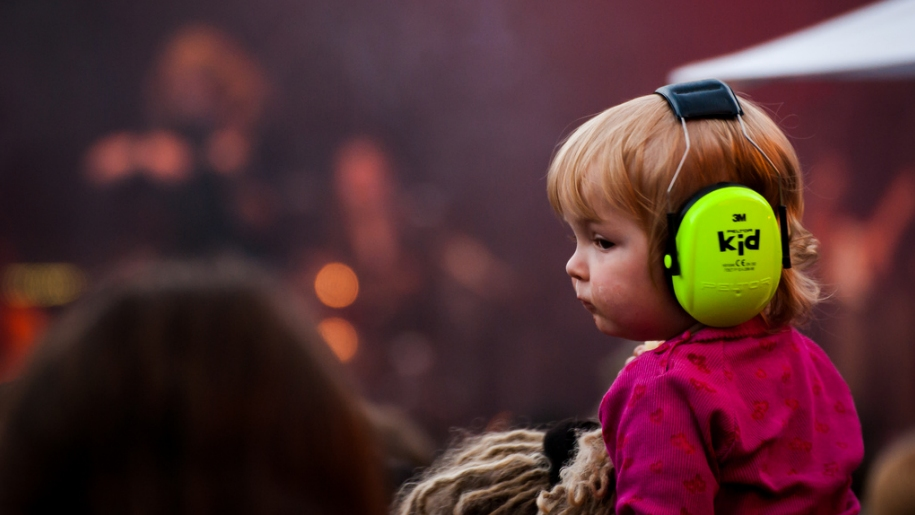 child at concert with ear protectors