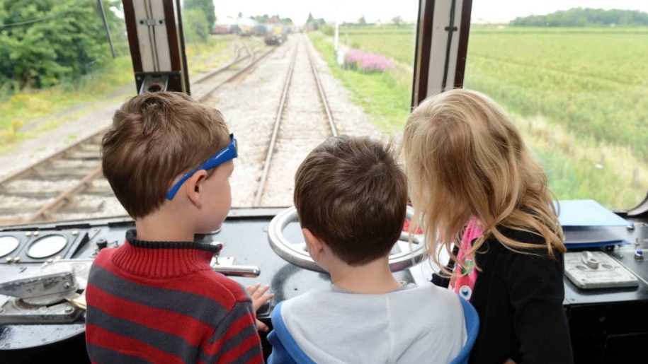 children in train driver seat