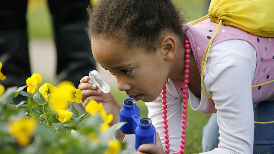 girl inspecting flowers with magnifying glass