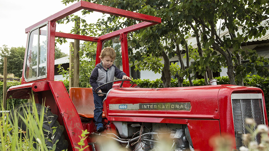 little boy play with disused tractor