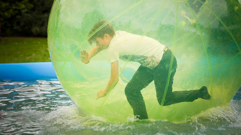 child in inflatable ball on water