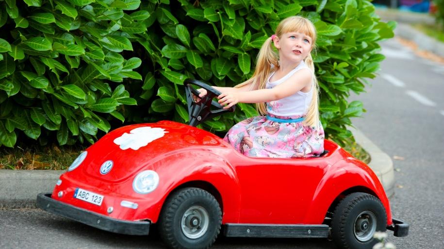 girl in toy car