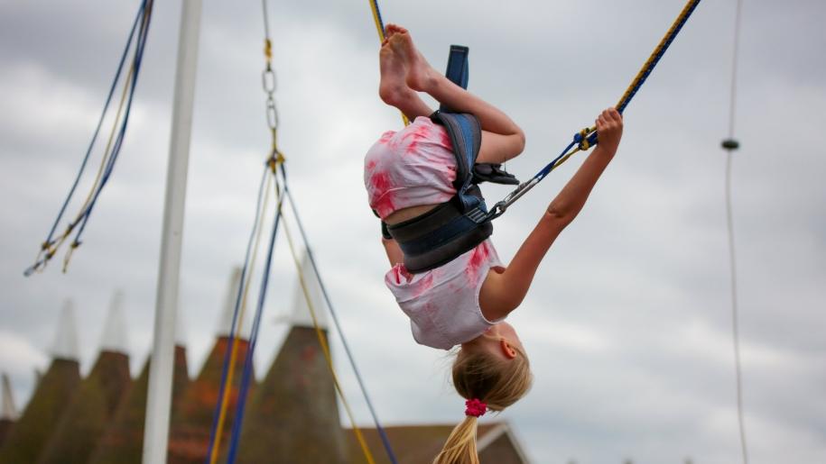 girl on trampoline harness