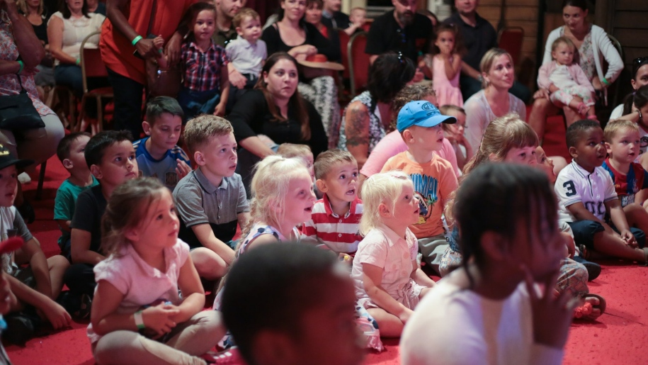children sitting on floor watching stage