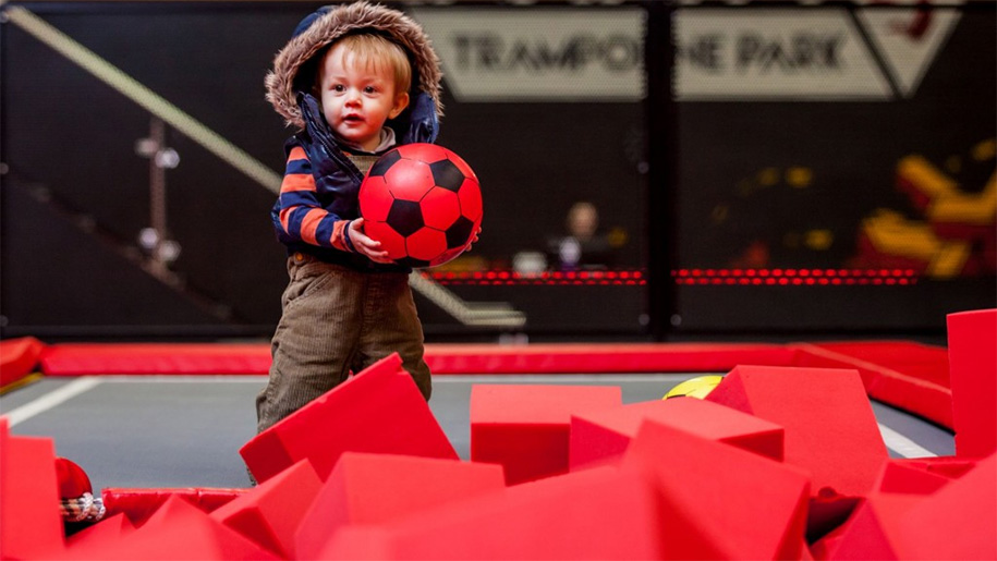 little boy with ball on trampoline
