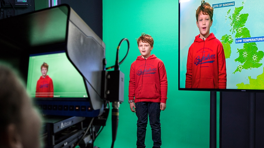 boy in red jumper doing the weather