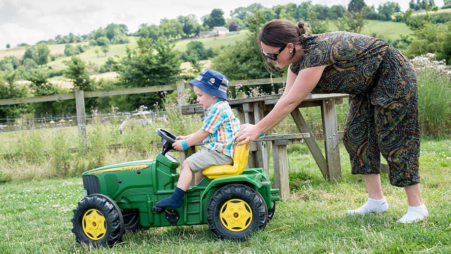 boy being pushed on toy tractor