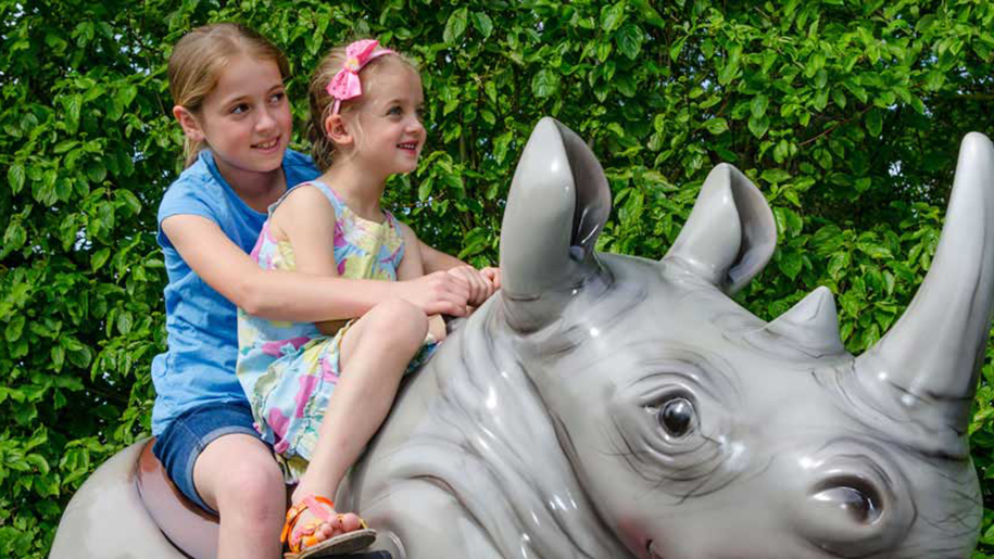 Longleat kids playing on a toy rhino