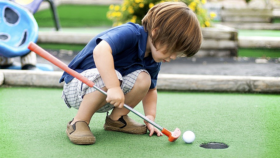 small boy putting golf ball