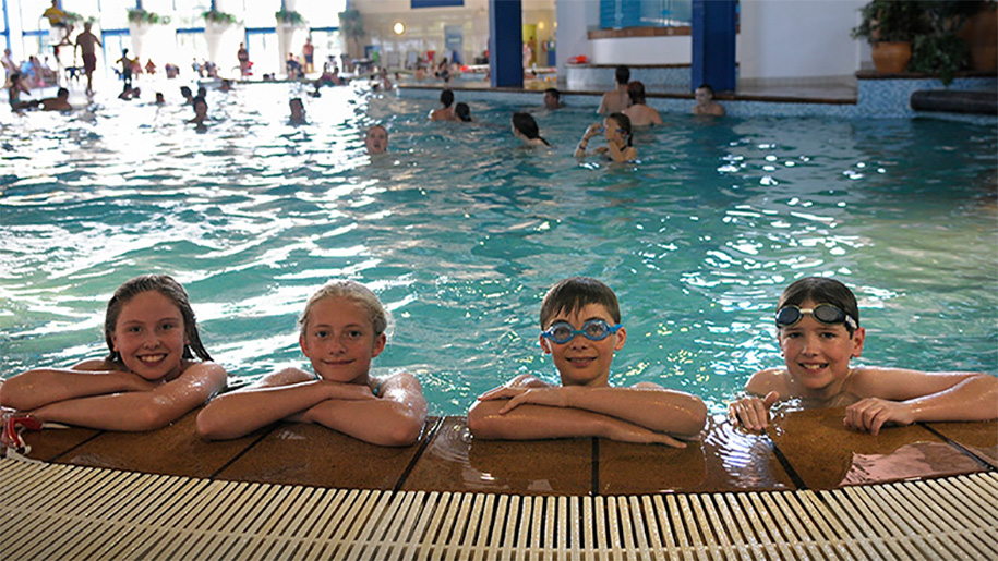 children smiling on the side of the swimming pool