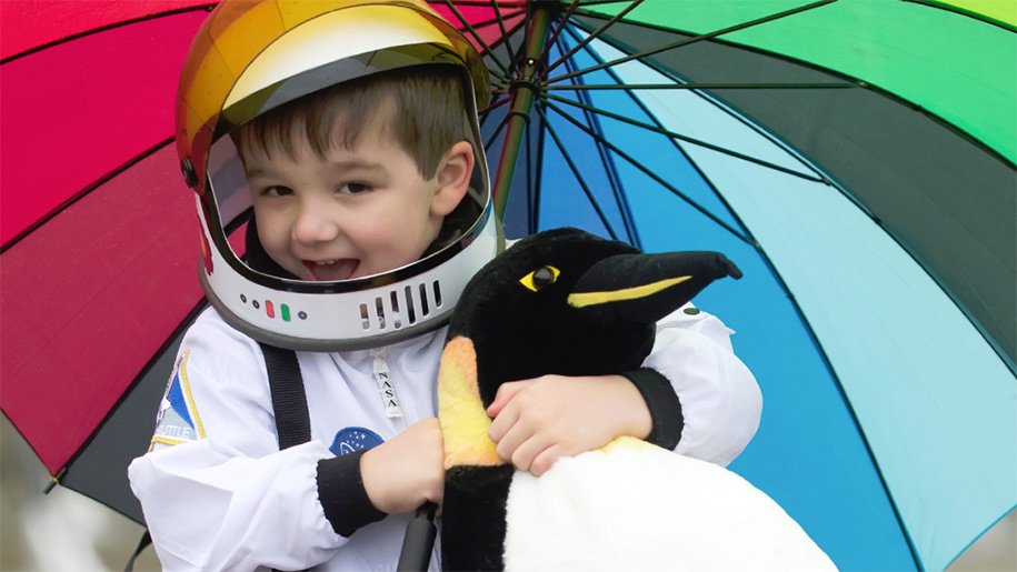 boy dressed are astronaut holding penguin