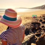 girl in sunhat on beach at sunset