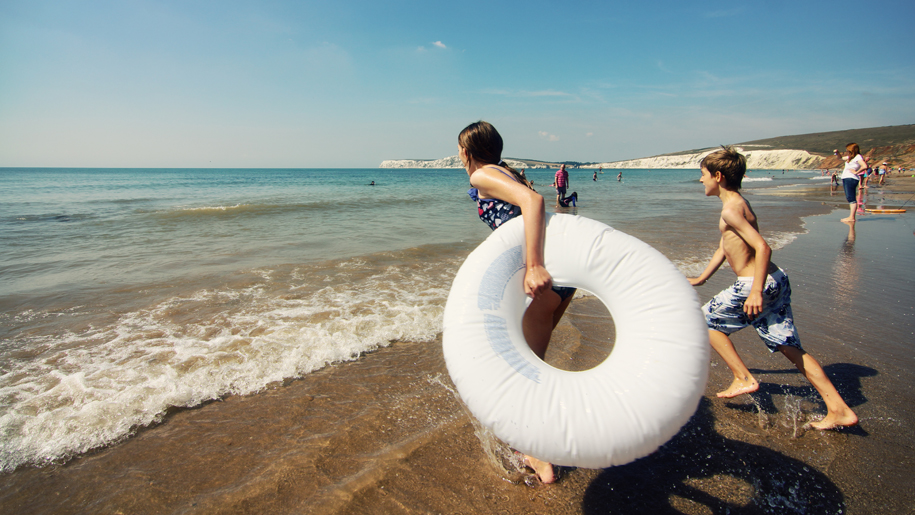 girl with rubber ring heading into sea